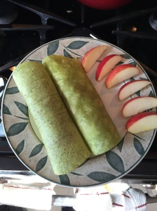 The plated chicken wraps with fresh fruit.