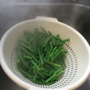 After being blanched for five minutes, the green beans have been poured into a colander.