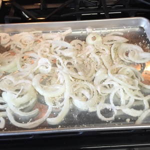 The coated onion slices  spread out on the oiled baking sheet.