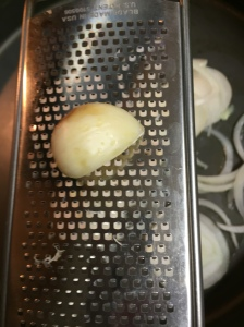 The onions have been introuduced into the skillet and I'm about to grate the garlic into the skillet (I prefer grating garlic than chopping or mincing and I because I love garlic I'm not worried with ending up with more than 1 Tbs of it in this dish).