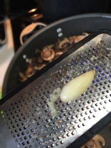 Grating one of the two cloves of garlic into the mushrooms.