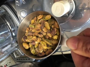 Adding the pistachios into the processor.