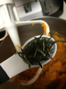 The first tsp of rosemary being added into the sweet potato mash.
