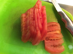 The tomato, having been sliced.