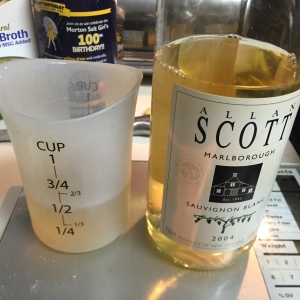 Measuring out half a cup of white wine.