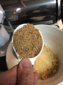 The ground pecans being added into the bowl with the cookie crumbs.