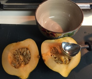 The acorn squash halves, about to be cleaned out with an ice cream scoop.
