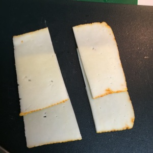 Slice two pieces of Muenster cheese in half.