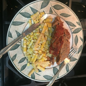 Two servings of the meatloaf plated with steamed corn.