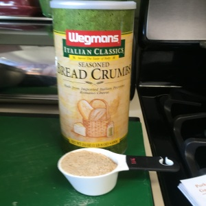 Portioning out one quarter of a cup of the bread crumbs that will be stirred into the mixture.