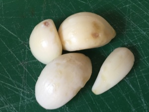 Getting the peeled garlic ready to be minced (well, grated in my kitchen).