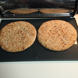 Here are two tasty pieces of flatbread, about to be sliced in half and then broiled.