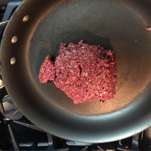 Into the skillet goes the ground beef.