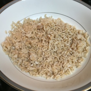 Half of the brown rice pouch layers the bottom of one dinner bowl.