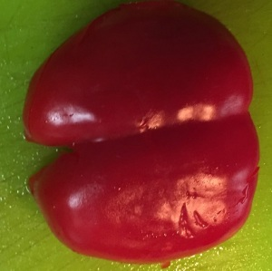 A relatively flattened bell pepper half, read to be sliced.