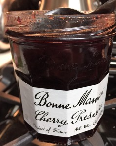 Cherry preserves should be easily found in the jelly and jams section of your grocery store.